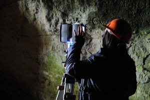 A woman conducting Terrestrial Laser Scanning inside the Sculptor's Cave